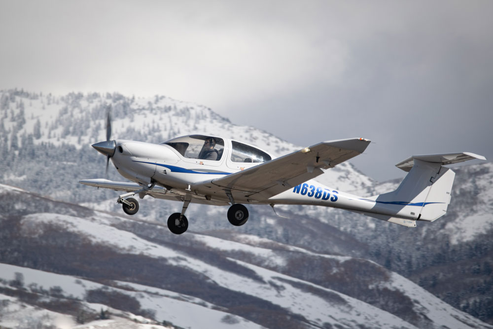 private plane flying with mountains in the background
