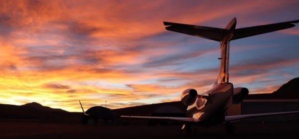 Airplane taking off runway at sunset